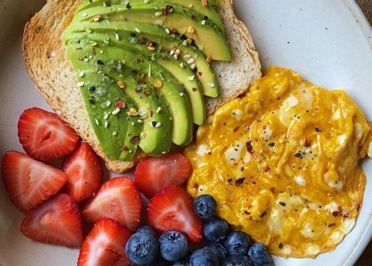 Tostada de aguacate con ración de frutas y huevo revuelto