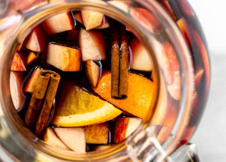 Jarra con trozos de manzana, rebanadas de naranja, jugo de frutas y canela